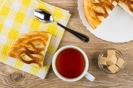Piece of pie with cottage cheese, teaspoon on napkin, tea, sugar in bowl on wooden table. Top view Stock Photo