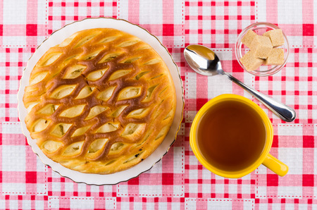 Wicker pie with cottage cheese in plate, cup of tea, sugar in bowl and teaspoon on checkered tablecloth. Top view