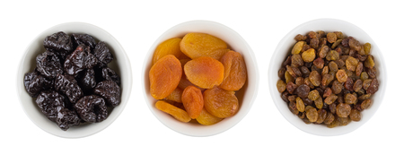 Three white bowls with prunes, dried apricots and raisins isolated on white background. Top view 版權商用圖片