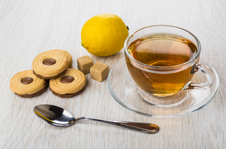 Cookies with chocolate stuffed, sugar, lemon, cup of tea on saucer and teaspoon on wooden table