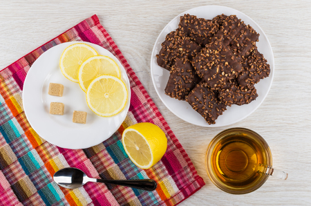 Cookies with chocolate and nuts in plate, lemon, sugar, spoon on napkin, tea on wooden table. Top view
