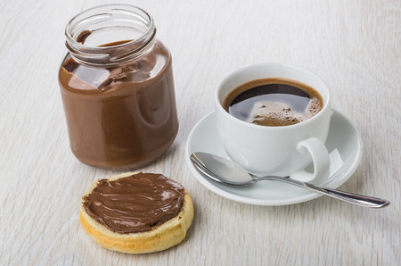 Sandwich with nut-chocolate paste, jar of paste, black coffee in cup and spoon on saucer on wooden table