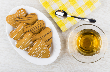 Shortbread cookies in form heart in dish, napkin, cup of tea, teaspoon on wooden table. Top view Stock Photo