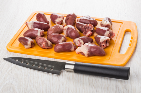 Raw chicken hearts on orange cutting board and kitchen knife on wooden table