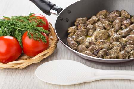 Fried chicken hearts in frying pan, tomatoes and dill in wicker basket, plastic spoon on wooden table