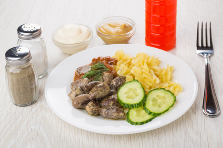 Plate with fried chicken hearts, pasta, baked eggplants, cucumbers, dill, bottle of ketchup, condiments, mustard, mayonnaise and fork on wooden table Stock Photo