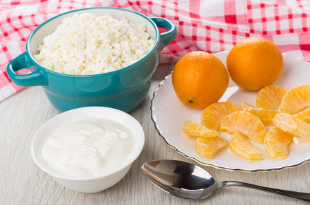 Cottage cheese in bowl, plate with tangerines, bowl with sour cream and spoon on wooden table Stock Photo