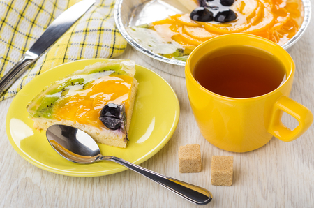 Piece of fruit pie in saucer, teaspoon, sugar, cup of tea, knife on napkin on wooden table Stock Photo