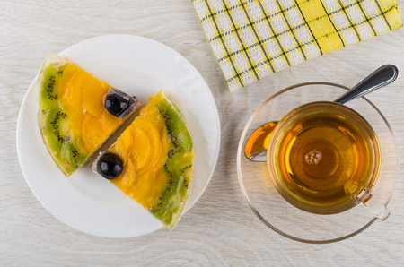 Two pieces of fruit pie in plate, napkin and cup of tea on wooden table. Top view