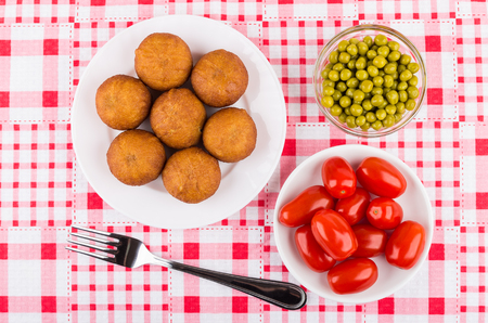 Small fried pies stuffed with meat in plate, greenpeas, tomato cherries and fork on checkered tablecloth