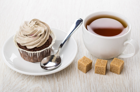 Cupcakes with brown cream, teaspoon in saucer, cup of tea, lumpy sugar on wooden table