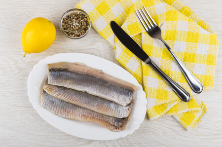 Fillet of herring in dish, knife and fork on napkin, lemon, condiment on wooden table. Top view