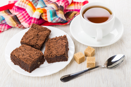Three pieces of chocolate cake in plate, sugar, cup of tea and teaspoon on wooden table