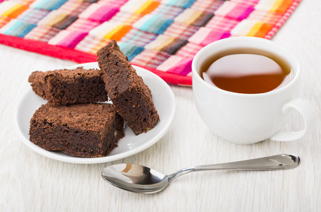 Pieces of chocolate cake in saucer, checkered napkin, cup of tea and teaspoon on wooden table