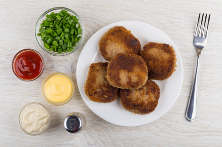 Fried cutlets in plate, bowls with chopped onion, mayonnaise, ketchup, horseradish, pepper and fork on wooden table. Top view