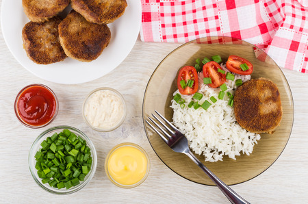 Fried cutlets with rice, tomatoes, green onion in brown plate, bowls with horseradish, mayonnaise, ketchup and fork on wooden table. Top view