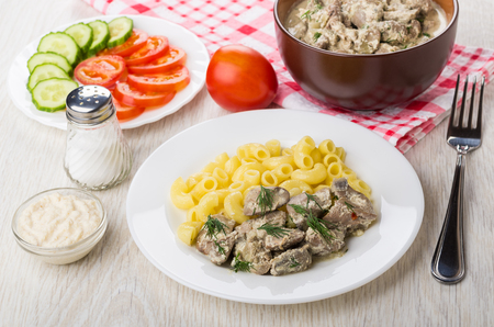 Chicken liver with pasta in plate, salt, horseradish, slices tomato, cucumber and fork on wooden table Stock Photo
