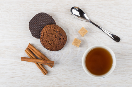 Oatmeal cookies with chocolate, teaspoon, brown sugar, cinnamon sticks and tea in cup on wooden table. Top view