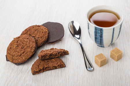 Heap of oatmeal cookies with chocolate bottom, teaspoon, brown sugar and tea in striped cup on wooden table