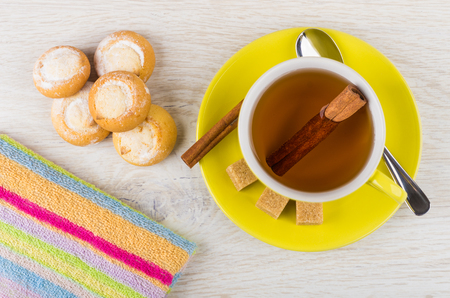 Cup of tea with cinnamon, teaspoon, sugar, cookies with cottage cheese and napkin on wooden table. Top view Stock Photo