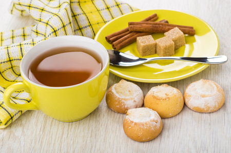 Cup of tea, sugar, cinnamon, teaspoon on saucer, cookies with cottage cheese filling and napkin on wooden table