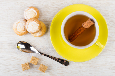 Cup of tea with cinnamon, teaspoon, sugar, cookies with cottage cheese filling on wooden table. Top view