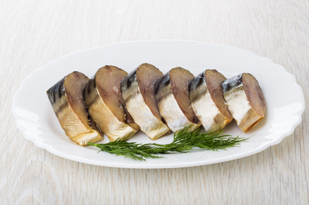 Slices of smoked mackerel with dill in white dish on wooden table Banco de Imagens