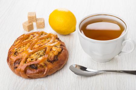 Wicker pie with chicken stuffed, cup of tea, lemon, lumpy sugar, teaspoon on wooden table Stock Photo
