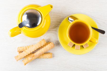 Teapot, cup of tea, spoon, sugar and flaky sticks on wooden table. Top view