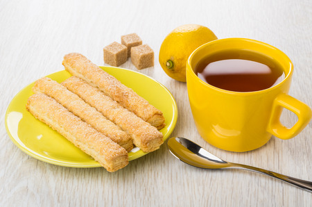 Sweet flaky sticks in yellow saucer, cup of tea, teaspoon, lemon, sugar on wooden table Stock Photo