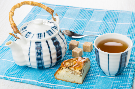 Piece of pie with chicken, teapot, sugar, cup of tea, teaspoon on blue napkin on wooden table Stock Photo