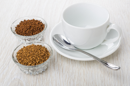 Bowls with instant freeze-dried, granulated coffee, empty cup, saucer and spoon on wooden table Stock Photo