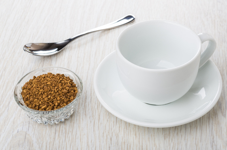 Bowl with instant freeze-dried coffee, empty cup, saucer and spoon on wooden table