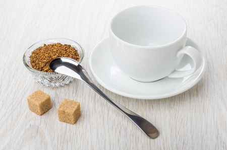 Bowl with instant freeze-dried coffee, cup, saucer, brown sugar and spoon on wooden table Stock Photo