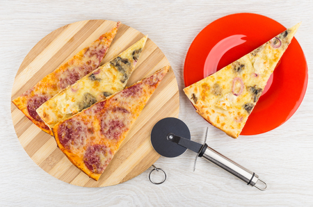 Pieces of pizza with chicken, mushroom, pepperoni on bamboo cutting board, in red plate, cutter on wooden table. Top view
