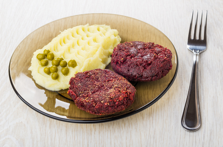 Cutlets from beetroot with mashed potato, green peas and fork on wooden table