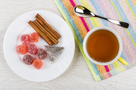 Red marmalade, teabag, cinnamon sticks in plate, cup of tea, teaspoon on napkin on wooden table. Top view