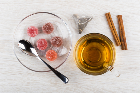 Red marmalade, teaspoon in saucer, teabag, cup of tea, cinnamon sticks on wooden table. Top view Stock Photo