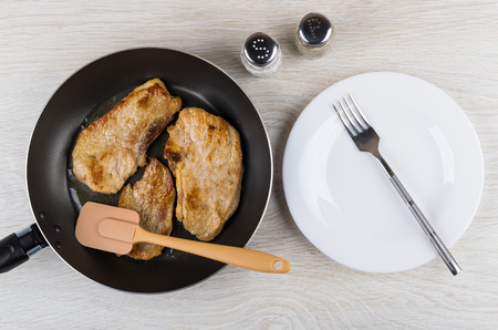Fried pork schnitzel in frying pan, spatula, salt, pepper, empty plate and fork on wooden table. Top view