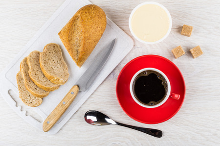 Red cup with coffee on saucer, melted cheese, sugar cubes, pieces of bread, knife on cutting board, spoon on wooden table. Top view