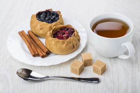 Pies with cowberries and blueberries, cinnamon sticks in plate, brown sugar, tea in cup, spoon on wooden table
