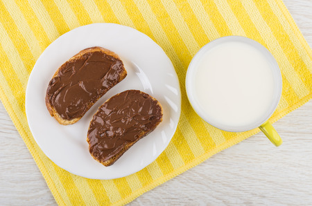 Sandwiches with melted chocolate cheese in plate, cup of milk on yellow napkin on wooden table. Top view