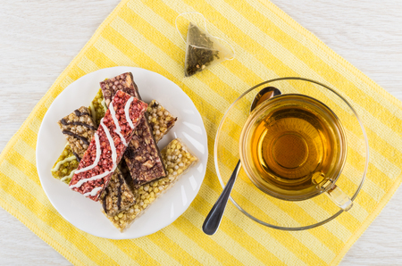 Heap of granola bars in plate, tea bag, cup of tea and spoon on napkin on wooden table. Top view