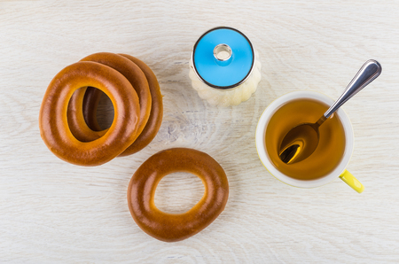 Stack of bread rings, cup of tea with spoon, sugar bowl on wooden table. Top view