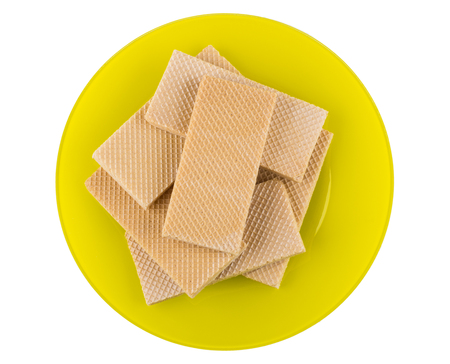 Heap of thin wafers in yellow plate isolated on white background. Top view