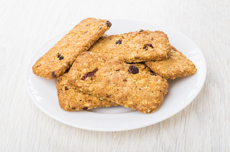 Cookies-muesli with cranberries and raisin in white plate on wooden table 免版税图像