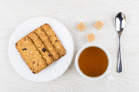 Cookies-muesli with cranberries and raisin in plate, cup of tea, sugar cubes, teaspoon on wooden table. Top view 免版税图像