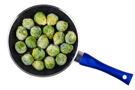 Frozen brussels sprouts in frying pan isolated on white background. Top view