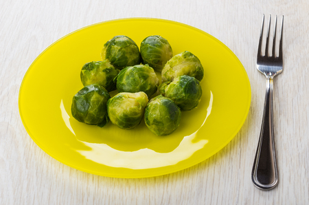 Cooked brussels sprouts in yellow plate and fork on wooden table