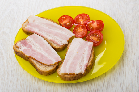 Sandwiches with bacon, pieces of tomatoes in yellow plate on wooden table Zdjęcie Seryjne